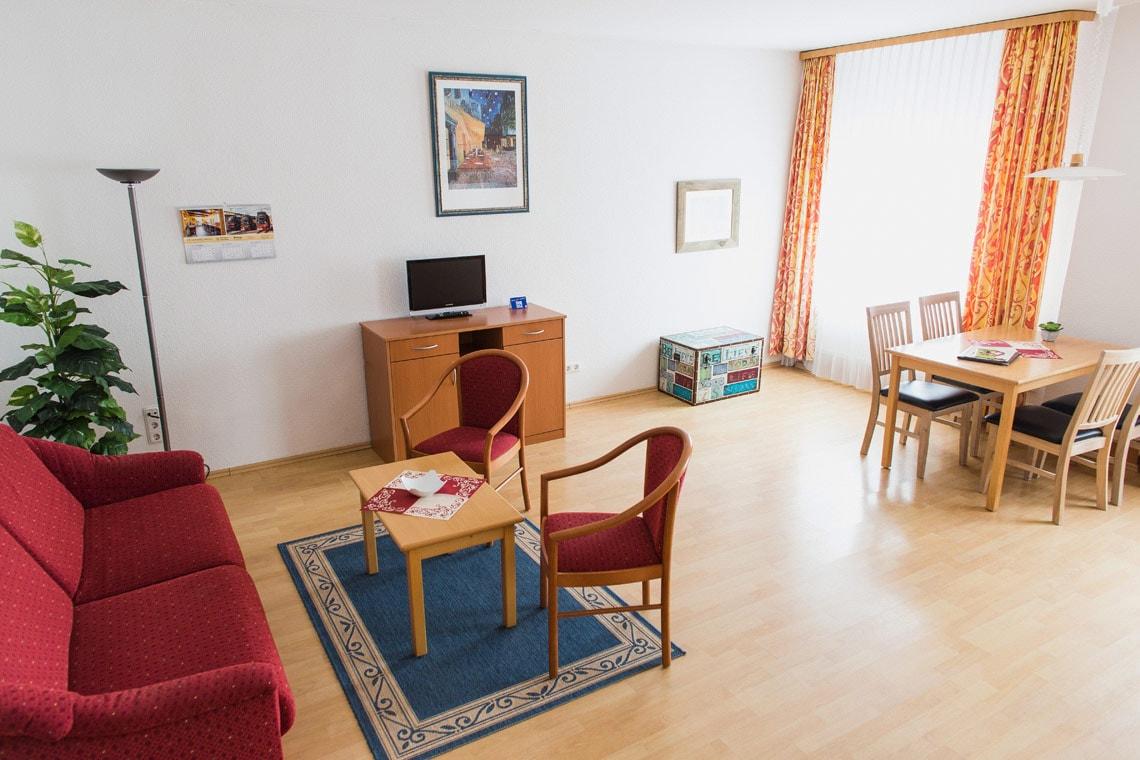Zu sehen sind die Sitzgelegenheiten sowie eine Komplettansicht des Wohnbereichs in den Appartments des Altwernigeröder Apparthotels.